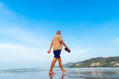 Middle aged man walking on a beach